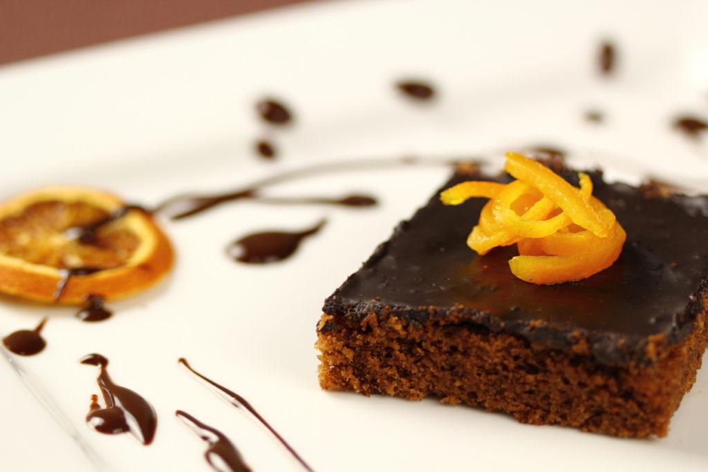 Fetta di torta al cioccolato con sopra scorze di arancia candite