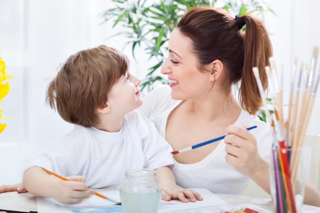 Mamma e figlio dipingono e sorridono insieme